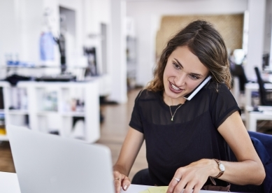 Woman on cell phone and working on laptop in office