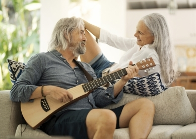 Mature Couple Playing Music on Couch